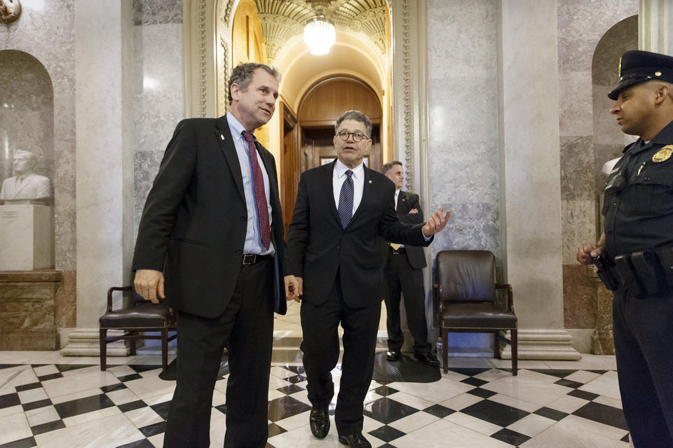 Photo - Sen. Sherrod Brown, D-Ohio, left, and Sen. Al Franken, D-Minn., leave the chamber during the vote on restoring jobless benefits for the long-term unemployed, legislation that expired late last year, at the Capitol in Washington, Monday, April 7, 2014. With their 17-day spring break beckoning at the end of the week, House and Senate lawmakers will have to scramble to reach agreement. (AP Photo/J. Scott Applewhite)
