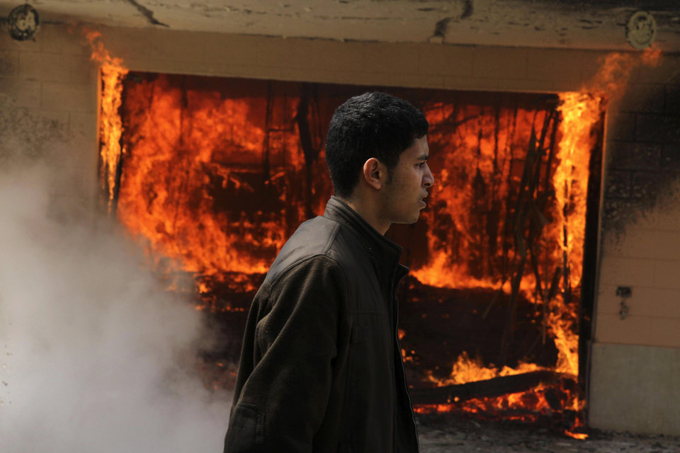 Photo - An Egyptian man walks on the grounds of a police officer's club as a fire set by protesters burns in Cairo, Egypt, Saturday, March 9, 2013. An Egyptian court on Saturday confirmed the death sentences against 21 people for taking part in a deadly soccer riot but acquitted seven police officials for their alleged role in the violence, touching off furious protests in Cairo that torched the soccer federation headquarters and a nearby police club.(AP Photo/Ahmed Gomaa)