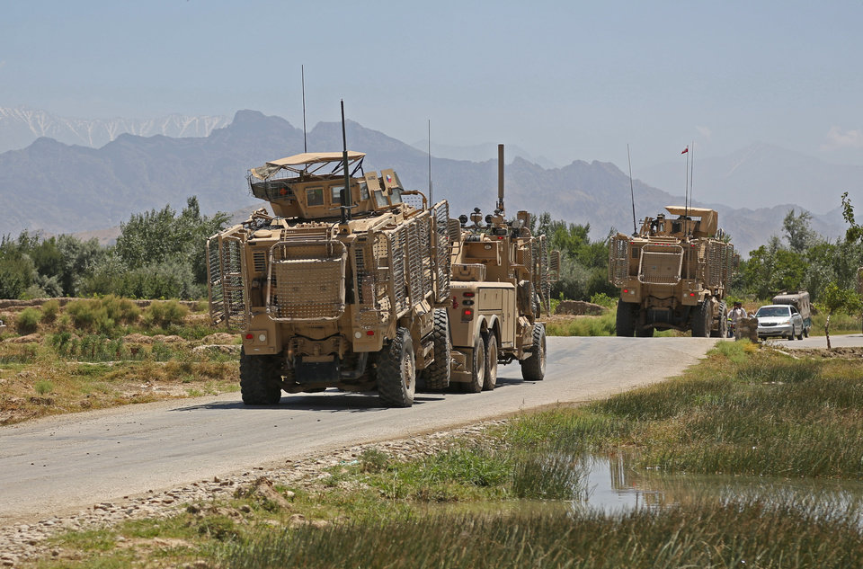 Photo - A NATO armored truck tows a vehicle damaged in a suicide attack in the Parwan province in eastern Afghanistan, Tuesday, July 8, 2014. An Afghan official says that at least 16 people, including four Czech soldiers, were killed Tuesday in a suicide attack near a clinic in eastern Afghanistan. A provincial spokesman says the others killed are at least 10 civilians and two police officers. The Taliban claimed responsibility for the attack in a statement sent to the media. The violence came as Afghanistan was mired in an electoral crisis after one of the candidates in the presidential elections, Abdullah Abdullah, refused to accept any results until millions of ballots are audited for fraud. (AP Photo/Rahmat Gul)