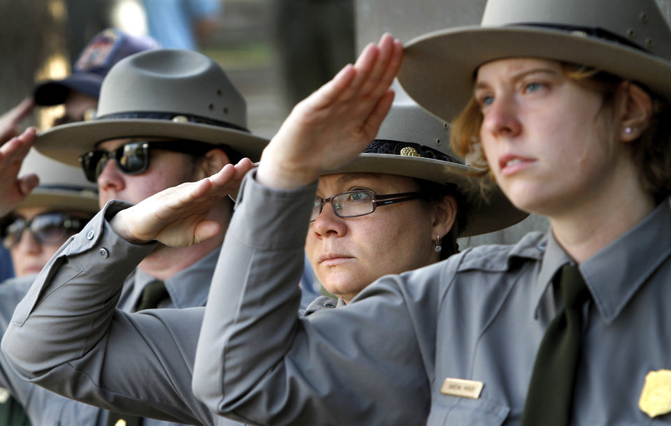 Photo - Park Rangers salute during the playing of the national anthem at the beginning of the ceremony. An estimated crowd of 2,000  attended the  Remembrance Ceremony to mark  the 17th anniversary of the 1995 bombing of the Alfred P. Murrah Federal Building in downtown Oklahoma City in which 168 people were killed.  Photo taken April 19, 2012.        Photo by Jim Beckel, The Oklahoman