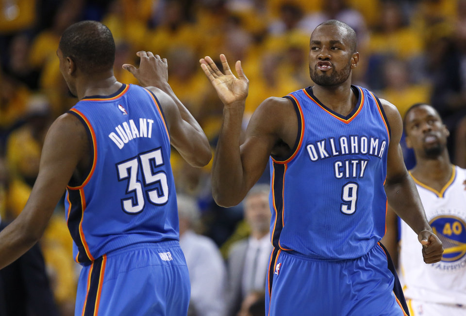 Photo - Oklahoma City's Serge Ibaka (9) celebrates with Oklahoma City's Kevin Durant (35) after making 3-pointer with during Game 5 of the Western Conference finals in the NBA playoffs between the Oklahoma City Thunder and the Golden State Warriors at Oracle Arena in Oakland, Calif., Thursday, May 26, 2016. Photo by Nate Billings, The Oklahoman
