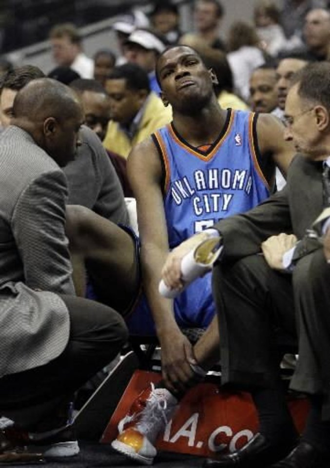 Photo - Oklahoma City Thunder guard  Kevin  Durant (35) holds his leg after injuring himself against the Dallas Mavericks during an NBA basketball game in Dallas, Friday, Feb. 27, 2009.  Durant left the game. (AP Photo/LM Otero)