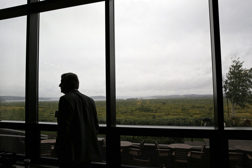 Photo - Peter Mooslechner, executive director and member of the Governing Board of the Central Bank of Austria, watches the rain outside during the Jackson Hole Economic Policy Symposium at the Jackson Lake Lodge in Grand Teton National Park near Jackson, Wyo. Friday, Aug. 22, 2014. (AP Photo/John Locher)