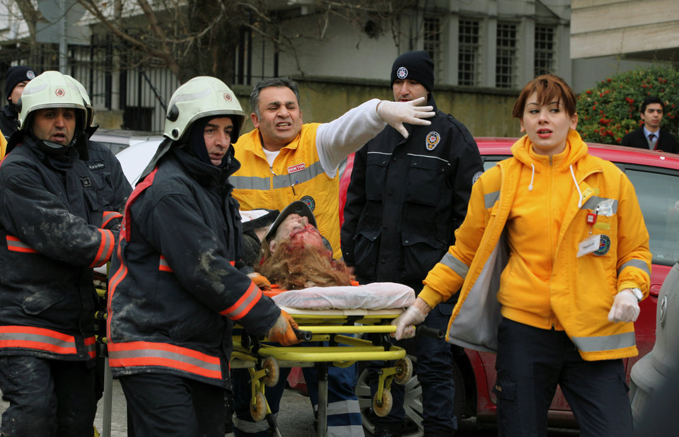 Medics carry an injured woman on a stretcher to an ambulance after a suspected suicide bomber detonated an explosive device at the entrance of the U.S. Embassy in the Turkish capital, Ankara, Turkey, Friday Feb. 1, 2013. The bomb appeared to have exploded inside the security checkpoint at the entrance of the visa section of the embassy. A police official said at least two people are dead. (AP Photo/Burhan Ozbilici)