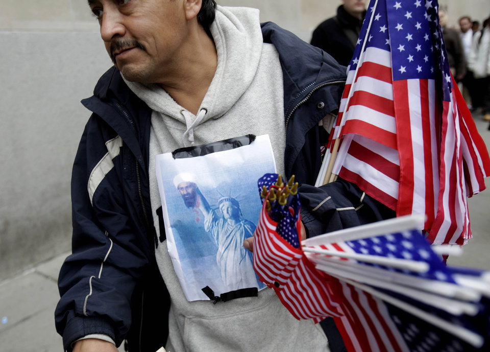 Photo - A poster showing the Statue of Liberty holding the head of Osama bin Laden is taped to Francisco Miranda's clothes as he sells flags at ground zero in New York, Monday, May 2, 2011. Joyous at the release of a decade's frustration, Americans streamed to the site of the World Trade Center, the gates of the White House and smaller but no less jubilant gatherings across the nation to celebrate the death of Osama bin Laden
