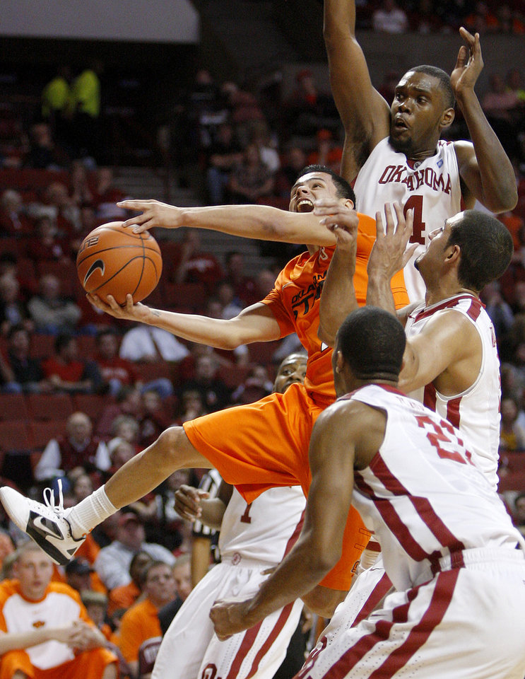 Photo - Oklahoma State's Cezar Guerrero goes to the basket as Oklahoma's Andrew Fitzgerald, top, C.J. Washington, and Cameron Clark defend during the Bedlam men's college basketball game between the University of Oklahoma Sooners and the Oklahoma State Cowboys in Norman, Okla., Wednesday, Feb. 22, 2012. Oklahoma won 77-64.  Photo by Bryan Terry, The Oklahoman
