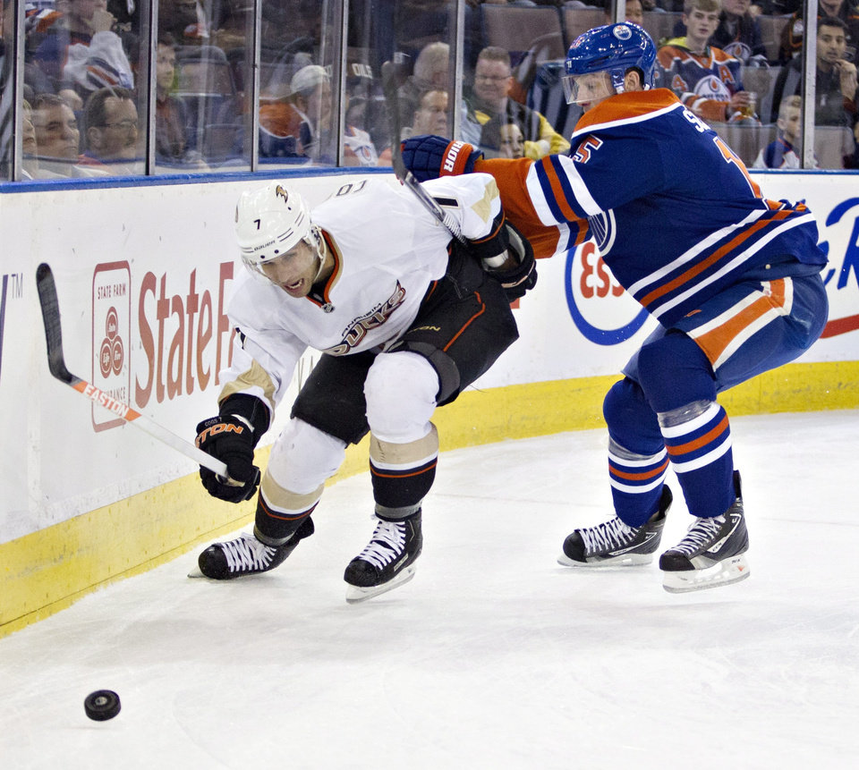 Photo - Anaheim Ducks' Andrew Cogliano (7) chases the puck as he is checked by Edmonton Oilers' Ladislav Smid during the first period of their NHL hockey game in Edmonton, Alberta, Sunday, April 21, 2013. (AP Photo/The Canadian Press, Jason Franson)