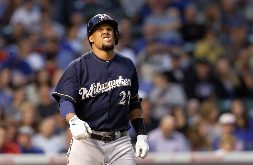 Photo - Milwaukee Brewers' Carlos Gomez reacts after being hit by a pitch from Chicago Cubs starting pitcher Kyle Hendricks during the third inning of a baseball game Tuesday, Aug. 12, 2014, in Chicago. (AP Photo/Charles Rex Arbogast)