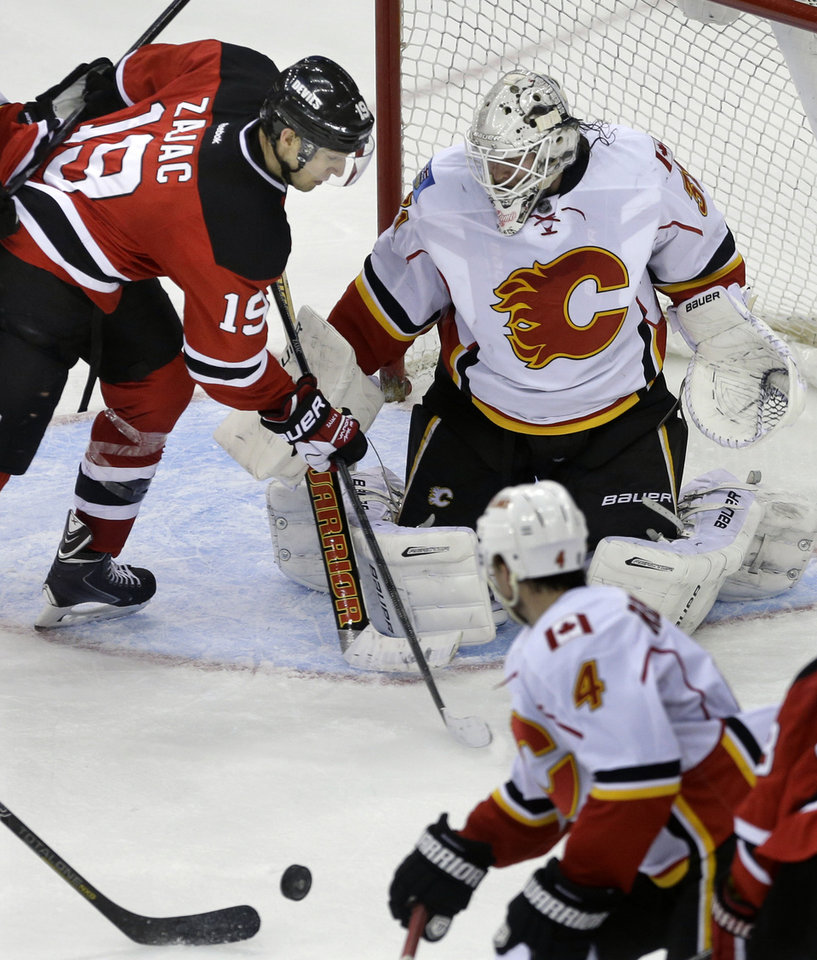 Photo - Calgary Flames goalie Karri Ramo, top right, of Finland, blocks a shot by New Jersey Devils' Travis Zajac (19)during the third period of an NHL hockey game in Newark, N.J., Monday, April 7, 2014. The Flames won 1-0. (AP Photo/Mel Evans)