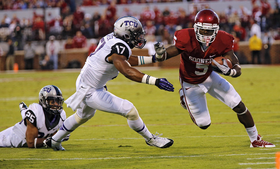 Photo - Oklahoma's Durron Neal (5) runs past TCU 's Sam Carter (17) during the college football game between the University of Oklahoma Sooners (OU) and the Texas Christian University Horned Frogs (TCU) at the Gaylord Family-Oklahoma Memorial Stadium on Saturday, Oct. 5, 2013 in Norman, Okla.   Photo by Chris Landsberger, The Oklahoman