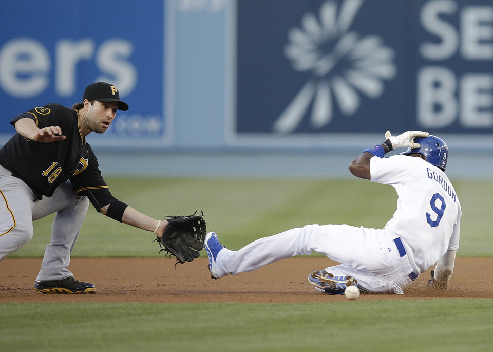 Photo - Los Angeles Dodgers' Dee Gordon, right, slides to steal second base as Pittsburgh Pirates second baseman Neil Walker waits for the throw during the first inning of a baseball game Friday, May 30, 2014, in Los Angeles. (AP Photo/Jae C. Hong)