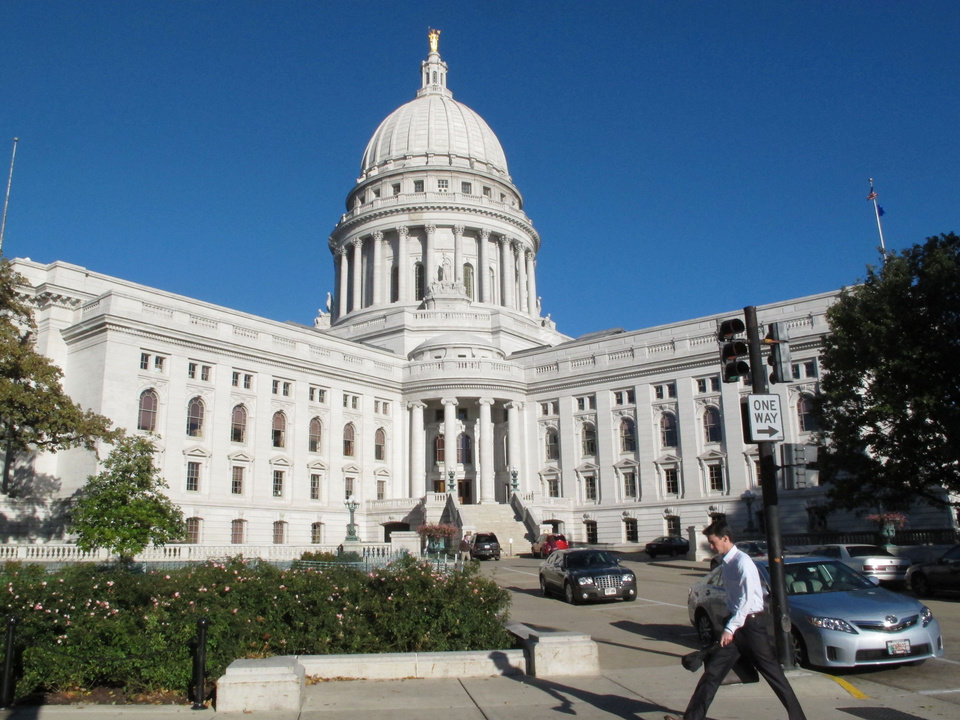 Photo - FILE - This Oct. 10, 2012 file photo shows a man walking by the Wisconsin state Capitol in Madison, Wis. The state Capitol, the highest point of Madison's modest skyline at just over 284 feet, marks both the geographic and cultural center of the city. (AP Photo/Scott Bauer, File)