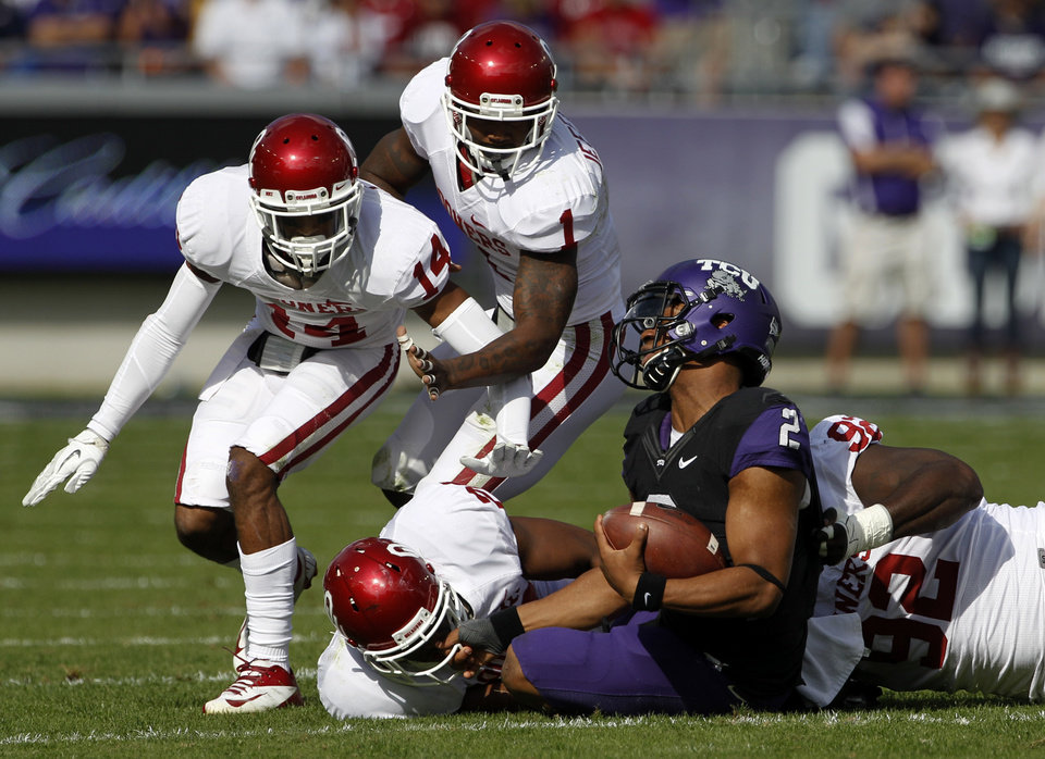 Photo - Oklahoma's Aaron Colvin (14), Tony Jefferson (1), Frank Shannon, bottom left, and Stacy McGee (92) combine to bring down TCU quarterback Trevone Boykin (2) in the first half of an NCAA college football game Saturday, Dec. 1, 2012, in Fort Worth, Texas. (AP Photo/Tony Gutierrez)