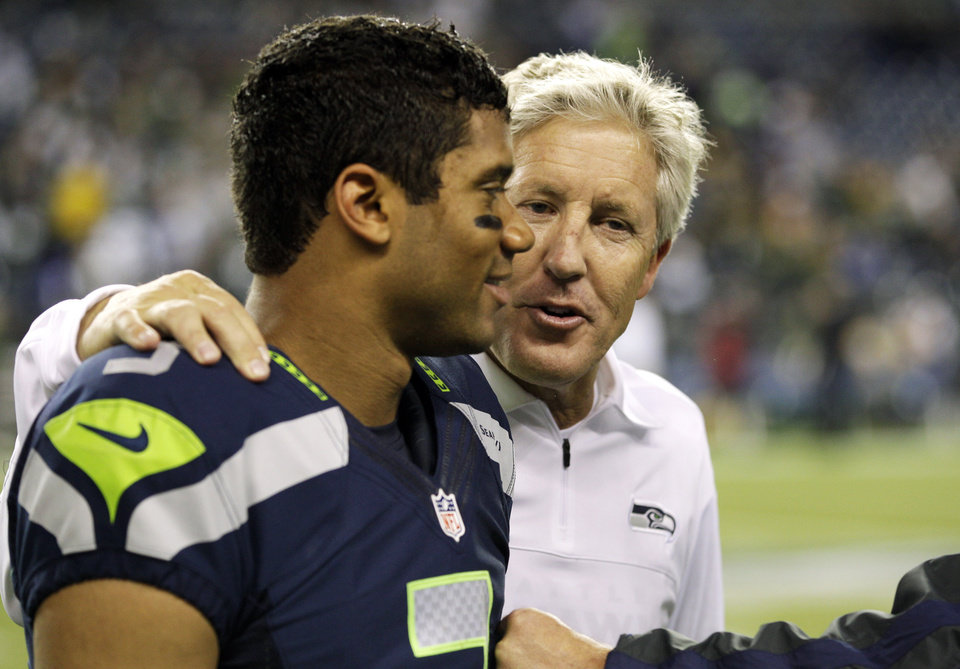 Photo -   Seattle Seahawks head coach Pete Carroll, right, walks with quarterback Russell Wilson after the Seahawks defeated the Green Bay Packers 14-12 in an NFL football game, Monday, Sept. 24, 2012, in Seattle. (AP Photo/Ted S. Warren)