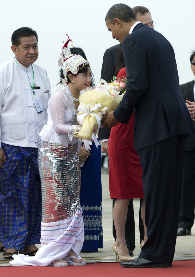 Photo -   U.S. President Barack Obama is presented with flowers as he arrives at Yangon International Airport in Yangon, Myanmar, on Air Force One, Monday, Nov. 19, 2012. This is the first visit to Myanmar by a sitting U.S. president. (AP Photo/Carolyn Kaster)