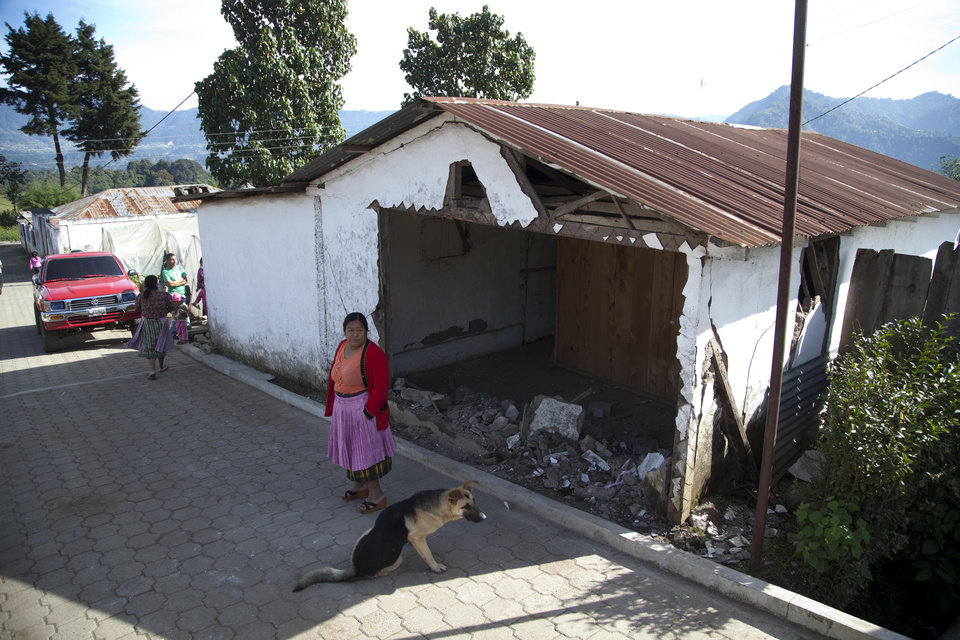 A resident stands outside a home that partially collapse during an earthquake, which authorities declared unsafe to live in, in San Cristobal Cucho, Guatemala, Thursday, Nov. 8, 2012. A magnitude 7.4 earthquake struck on Wednesday, killing at least 52 people and leaving dozens more missing. (AP Photo/Moises Castillo) ORG XMIT: GUA109