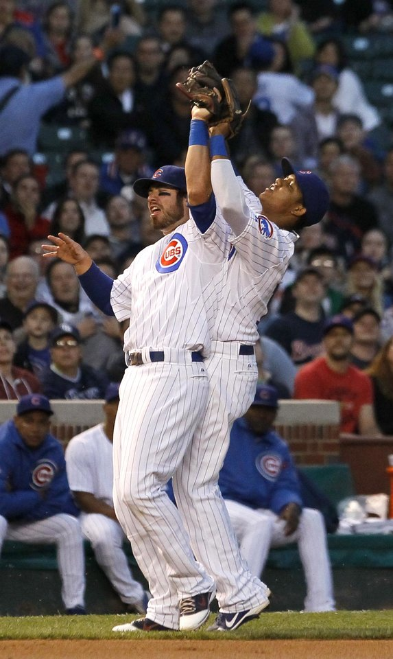 Photo -   Chicago Cubs third baseman Ian Stewart, left, and shortstop Starlin Castro, go after a pop up by Atlanta Braves' Michael Bourn, during the third inning of a baseball game Tuesday, May 8, 2012, in Chicago. (AP Photo/Charles Rex Arbogast)