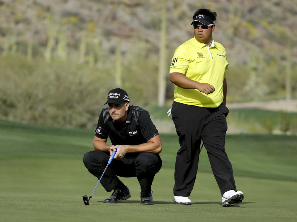 Photo - Henrik Stenson, left, of Sweden, and Kiradech Aphibanrat line up putts 16th hole during the first round of the Match Play Championship golf tournament on Wednesday, Feb. 19, 2014, in Marana, Ariz. Stenson won 2 and 1. (AP Photo/Ted S. Warren)