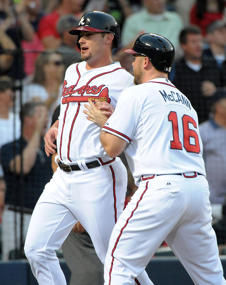 Photo - Atlanta Braves' Joey Terdoslavich, left, is congratulated by teammate Brian McCann (16) after they scored on an RBI triple by Elliot Johnson during the second inning of a baseball game against the Cleveland Indians at Turner Field, Tuesday, Aug. 27, 2013, in Atlanta. (AP Photo/David Tulis)