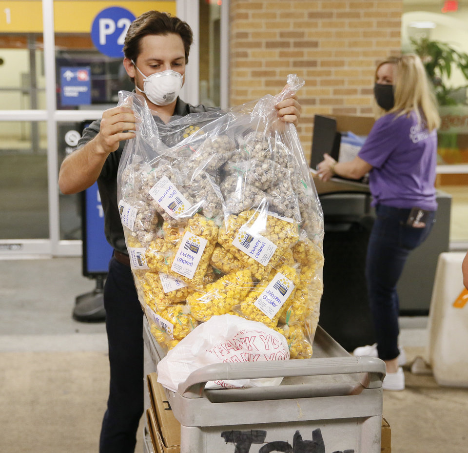 Photo - DJ Boles, owner of Oklahoma Gourmet Popcorn, places bags of gourmet popcorn on a cart outside the emergency room at The Children's Hospital in Oklahoma City, Sunday, April 26, 2020. Oklahoma's Credit Union purchased pizza from Empire Slice House and popcorn from Oklahoma Gourmet Popcorn for a popcorn and pizza party for night shift healthcare workers at the emergency room. The hospital also received healthcare mask extenders manufactured by entrepreneurs Ian and Hailey McDermid, owners of The Pump Bar and The Bunker Club. [Nate Billings/The Oklahoman]