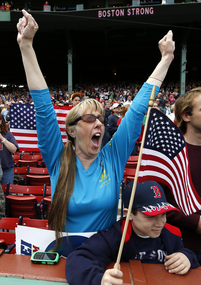 A fan cheers during a tribute to first responders to the Boston Marathon bombing before a baseball game between the Boston Red Sox and the Kansas City Royals in Boston, Saturday, April 20, 2013. (AP Photo/Michael Dwyer) ORG XMIT: MAMD111