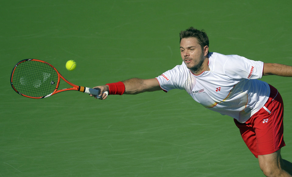 Photo - Stanislas Wawrinka, of Switzerland, returns a shot against Kevin Anderson, of South Africa, during a fourth round match at the BNP Paribas Open tennis tournament, Wednesday, March 12, 2014, in Indian Wells, Calif. (AP Photo/Mark J. Terrill)