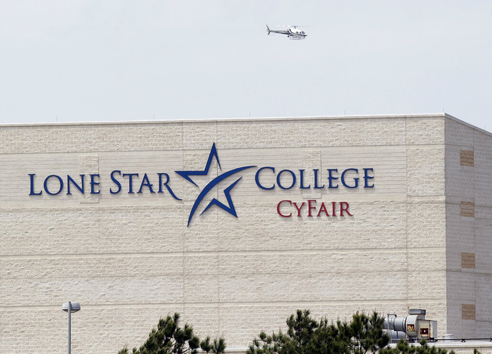 Photo - A police helicopter circles above the Cy-Fair campus of Lone Star Community College in Cypress, Texas, where officials say about a dozen people have been wounded in a stabbing attack Tuesday, April 9, 2013. The Harris County Sheriff's department confirmed at least 11 people wounded and that authorities have one suspect in custody. (AP Photo/Houston Chronicle, Melissa Phillip)