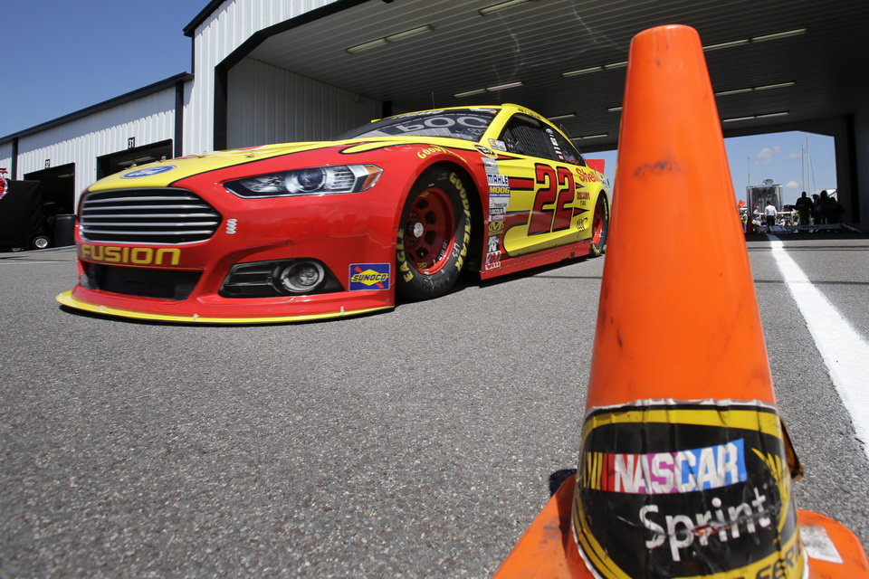 Photo - Joey Logano drives in the garage area during practice Friday Aug. 2, 2013, for Sunday's NASCAR Sprint Cup Series auto race in Long Pond, Pa. (AP Photo/Mel Evans)