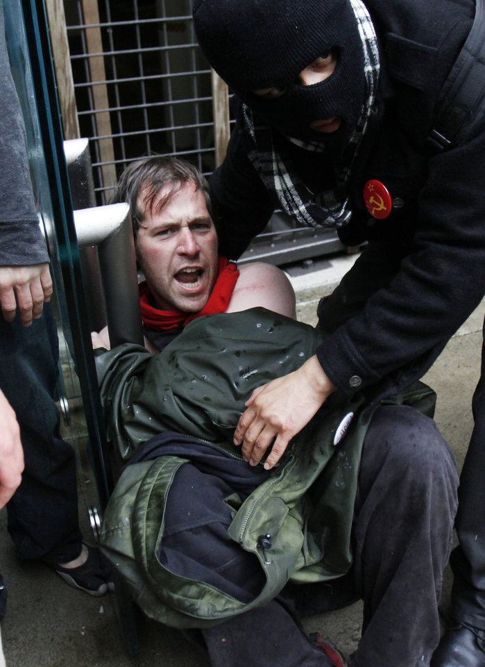 A protestor is assisted after a confrontation with police during a May Day march and protest in Portland, Ore., Tuesday, May 1, 2012. Hundreds of activists across the U.S. joined the worldwide May Day protests on Tuesday, with Occupy Wall Street members in several cities leading demonstrations against major financial institutions. (AP Photo/Don Ryan)