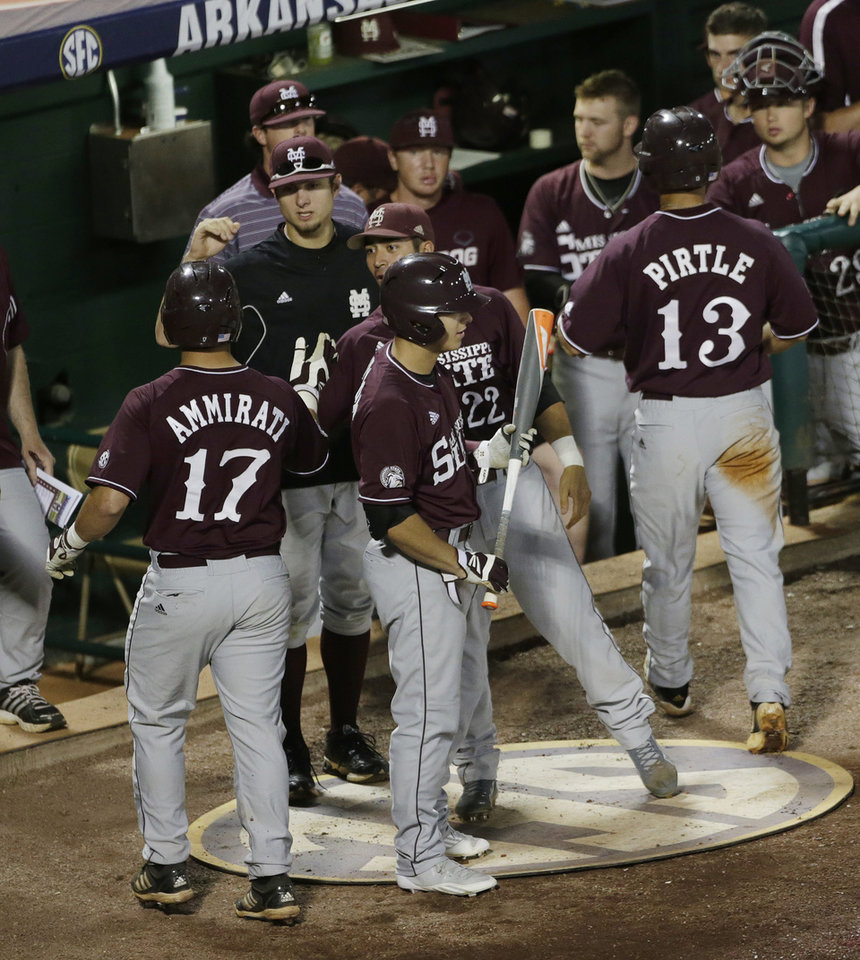 Photo - Mississippi State's Nick Ammirati (17) is congratulated along with teammate Brett Pirtle (13) after Ammirati hit a sacrifice fly to score Pirtle in the fourth inning of their Southeastern Conference Tournament baseball game against Texas A&M at the Hoover Met in Hoover, Ala., Thursday, May 23, 2013. (AP Photo/Dave Martin)