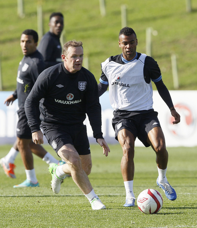 Photo -   England soccer players Wayne Rooney, left, and Ashley Cole vie for the ball during a training session at England new training facility at St George's Park near Burton Upon Trent England,Tuesday, Oct. 9, 2012. England play San Marino in a World Cup qualifier on Friday.(AP Photo/Kirsty Wigglesworth)