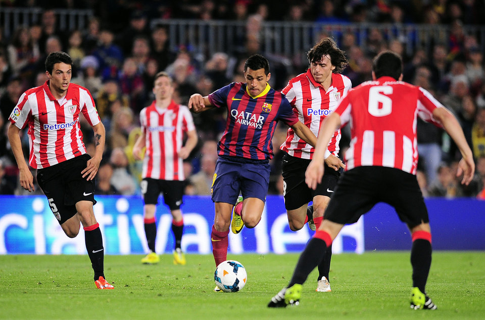 Photo - FC Barcelona's Alexis Sanchez, from Chile, center, duels for the ball against Athletic Bilbao's Ander Iturraspe, second right, during a Spanish La Liga soccer match at the Camp Nou stadium in Barcelona, Spain, Sunday April 20, 2014. (AP Photo/Manu Fernandez)