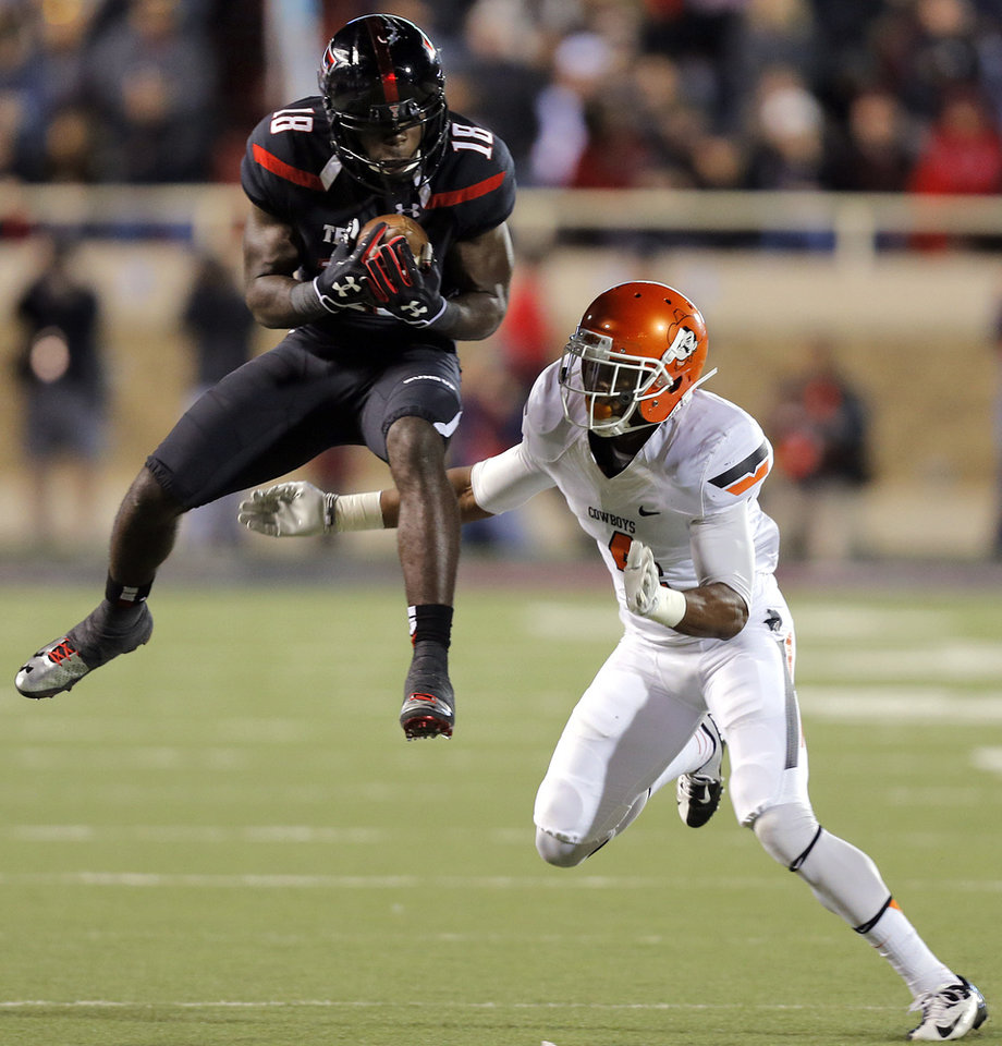 Texas Tech's Eric Ward (18) makes a catch in front ofOklahoma State 's Justin Gilbert (4) during the college football game between the Oklahoma State University Cowboys (OSU) and the Texas Tech University Red Raiders (TTU) at Jones AT&T Stadium in Lubbock, Tex. on Saturday, Nov. 2, 2013.  Photo by Chris Landsberger, The Oklahoman
