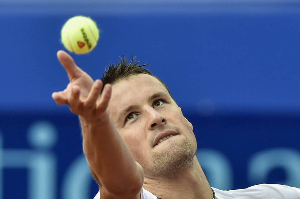 Photo - Kenny De Schepper of France serves a ball to Mikhail Youzhny of Russia during the second round match at the Suisse Open tennis tournament in Gstaad, Switzerland, Thursday, July 24, 2014. (AP Photo/Keystone,Peter Schneider)