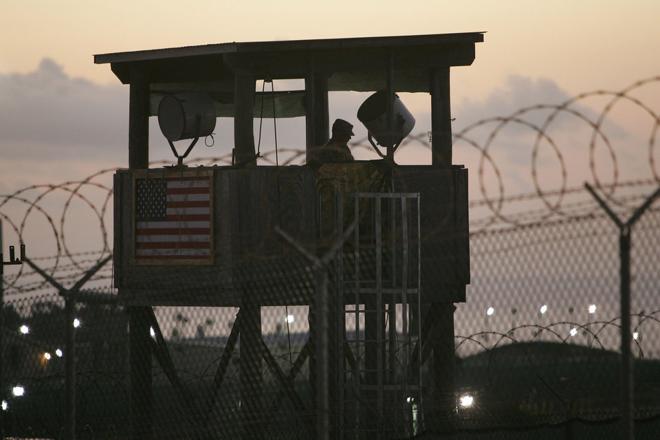 Photo - FILE - In this Dec. 7, 2006 file photo reviewed by the U.S. Military, a U.S. soldier keeps watch from a guard tower overlooking Camp Delta detention center on Guantanamo Bay U.S. Naval Base in Cuba. Lawyers for Guantanamo prisoners charged in the Sept. 11 attack say the FBI has questioned more people who work as support staff on their legal teams than previously disclosed, a development that may prompt a new detour in an already snarled case when the war crimes tribunal reconvenes Monday at the U.S. base in Cuba. A judge will consider a delay in the proceedings in a hearing on Monday, June 16, 2014. (AP Photo/Brennan Linsley, File)