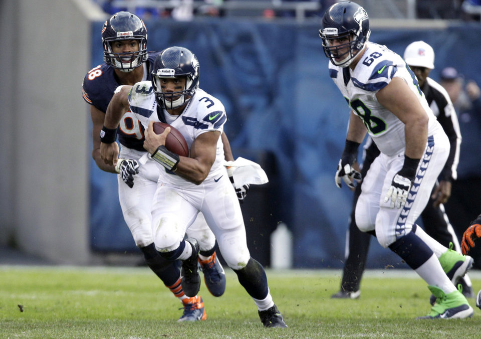 Photo - Seattle Seahawks quarterback Russell Wilson (3) rushes past Chicago Bears defensive end Corey Wootton (98) during the second half of an NFL football game in Chicago, Sunday, Dec. 2, 2012. (AP Photo/Nam Y. Huh)