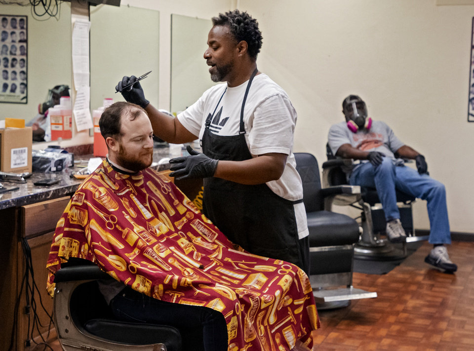 Photo - Barber Michael Mitchell cuts the hair of The Oklahoma's David Dishman at Versatile Styles Barber Shop located at 9132 S. Walker Ave. on Tuesday, May 5, 2020, in Oklahoma City, Okla. . [Chris Landsberger/The Oklahoman]