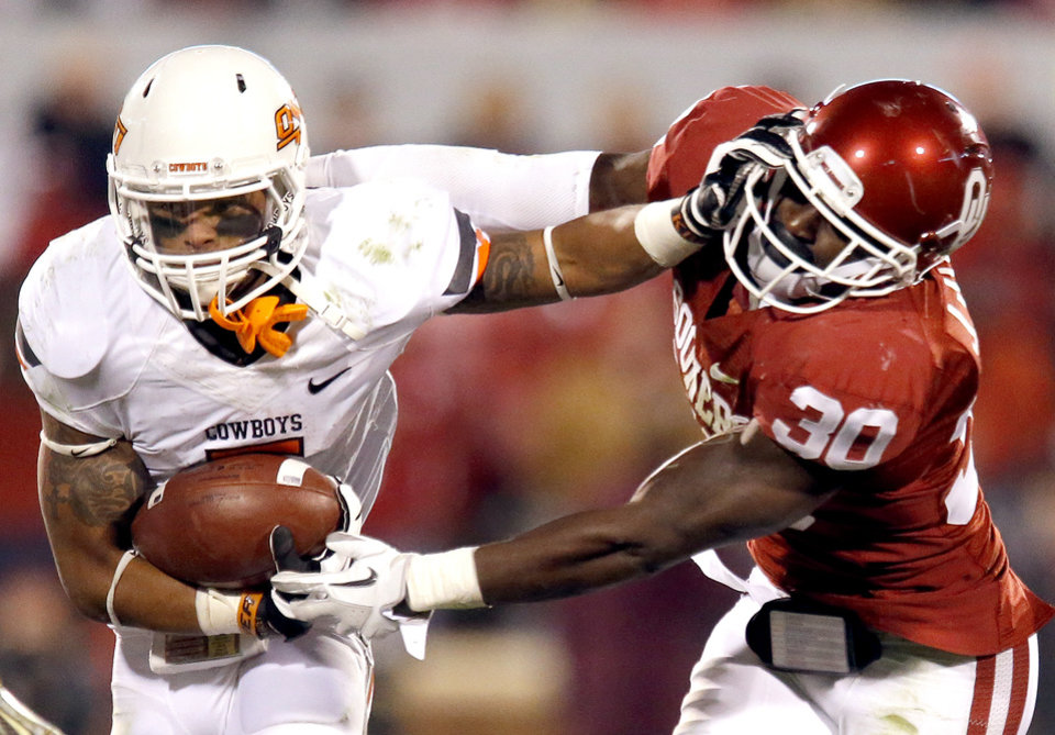 Photo - Oklahoma State's Josh Stewart (5) stiff arms Oklahoma's Javon Harris (30) during the Bedlam college football game between the University of Oklahoma Sooners (OU) and the Oklahoma State University Cowboys (OSU) at Gaylord Family-Oklahoma Memorial Stadium in Norman, Okla., Saturday, Nov. 24, 2012. OU won 51-48 in overtime. Photo by Sarah Phipps, The Oklahoman