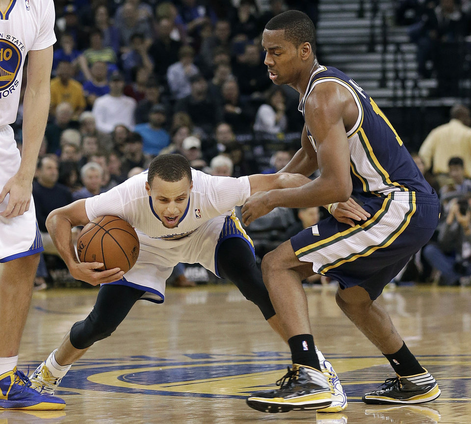 Photo - Golden State Warriors shooting guard Stephen Curry, left, tries to dribble past Utah Jazz point guard Alec Burks during the second quarter of an NBA basketball game in Oakland, Calif., Saturday, Nov. 16, 2013. (AP Photo/Jeff Chiu)