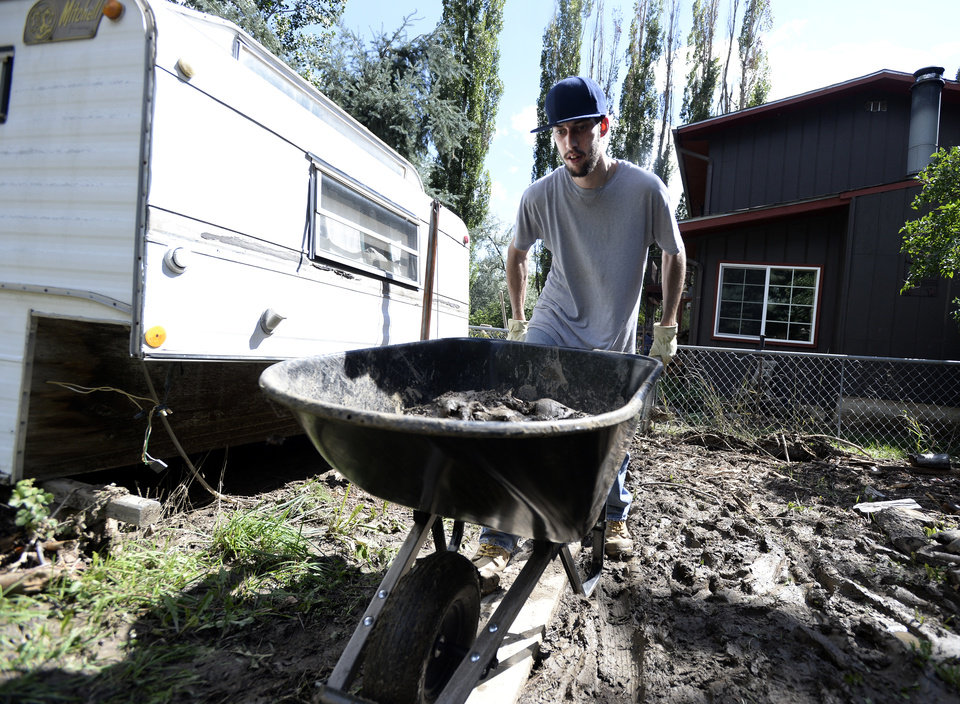 Photo - Jestin Franklin pushes a wheelbarrow full of mud while helping his grandmother clean flood damage at her home on Tuesday, Sept. 17,  2013 in the Fourmile Canyon area of Boulder County Colorado. (AP Photo/Daily Camera, Jeremy Papasso)