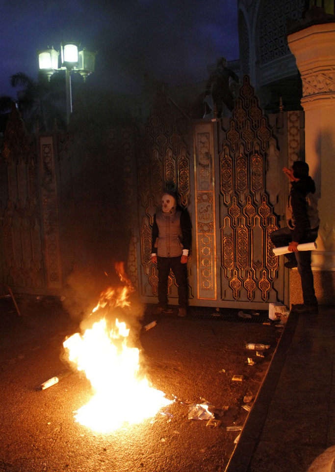 Photo - A bonfire burns as masked protesters stand at the gate outside Egypt's presidential palace in Cairo, Friday, Feb. 1, 2013. Thousands of protesters denouncing Egypt's Islamist president marched on his palace in Cairo on Friday, clashing with security forces firing tear gas and water cannons in the eighth day of the country's wave of political violence. (AP Photo/Mostafa El Shemy)