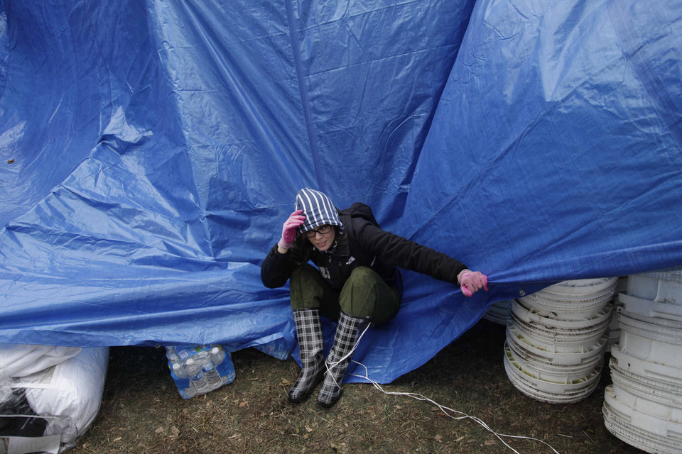 Gina Kohm tries to keep a tarp from blowing away which covers a pile of donated supplies at an aid station in the New Dorp section of Staten Island, New York, Wednesday, Nov. 7, 2012. Residents of New York and New Jersey who were flooded out by Superstorm Sandy are waiting with dread Wednesday for the second time in two weeks as another, weaker storm heads toward them and threatens to inundate their homes again or simply leave them shivering in the dark for even longer. (AP Photo/Seth Wenig) ORG XMIT: NYSW101