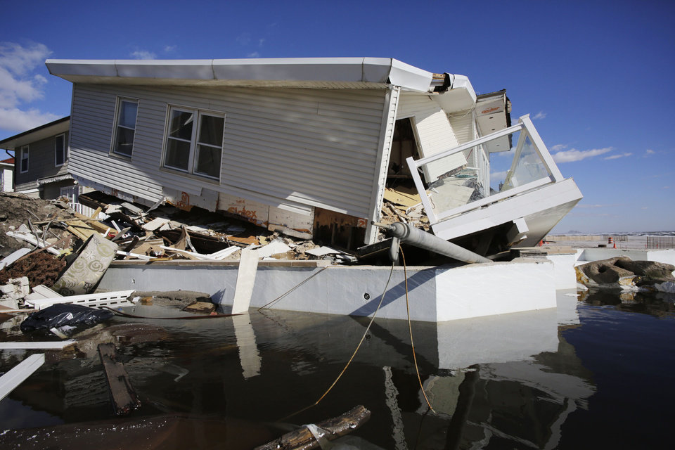 A storm-damaged beachfront house is reflected in a pool of water in the Far Rockaways, Thursday, Jan. 31, 2013 in the Queens borough of New York. Three months after Superstorm Sandy ravaged coastal areas in much of the Northeast, Congress on Monday, Jan. 28 passed a $50.5 billion emergency aid package for storm victims. (AP Photo/Mark Lennihan)