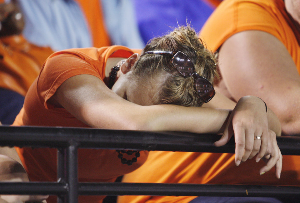 Fan Danielle Brawner hides her head during second half action during the college football game between the Troy University Trojans and the Oklahoma State University Cowboys at Movie Gallery Veterans Stadium in Troy, Ala., Friday, September 14, 2007. BY STEVE SISNEY, THE OKLAHOMAN