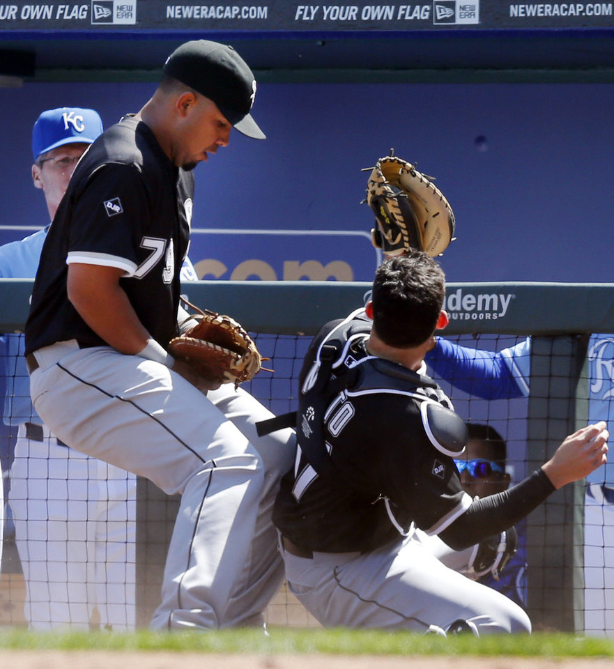Photo - Chicago White Sox first baseman Jose Abreu (79) catches a foul ball between his legs while backing up Chicago White Sox catcher Adrian Nieto, right, during the third inning of a baseball game against the Kansas City Royals at Kauffman Stadium in Kansas City, Mo., Saturday, April 5, 2014. The foul ball was hit by Kansas City Royals' Alcides Escobar who was out on the play. (AP Photo/Orlin Wagner)