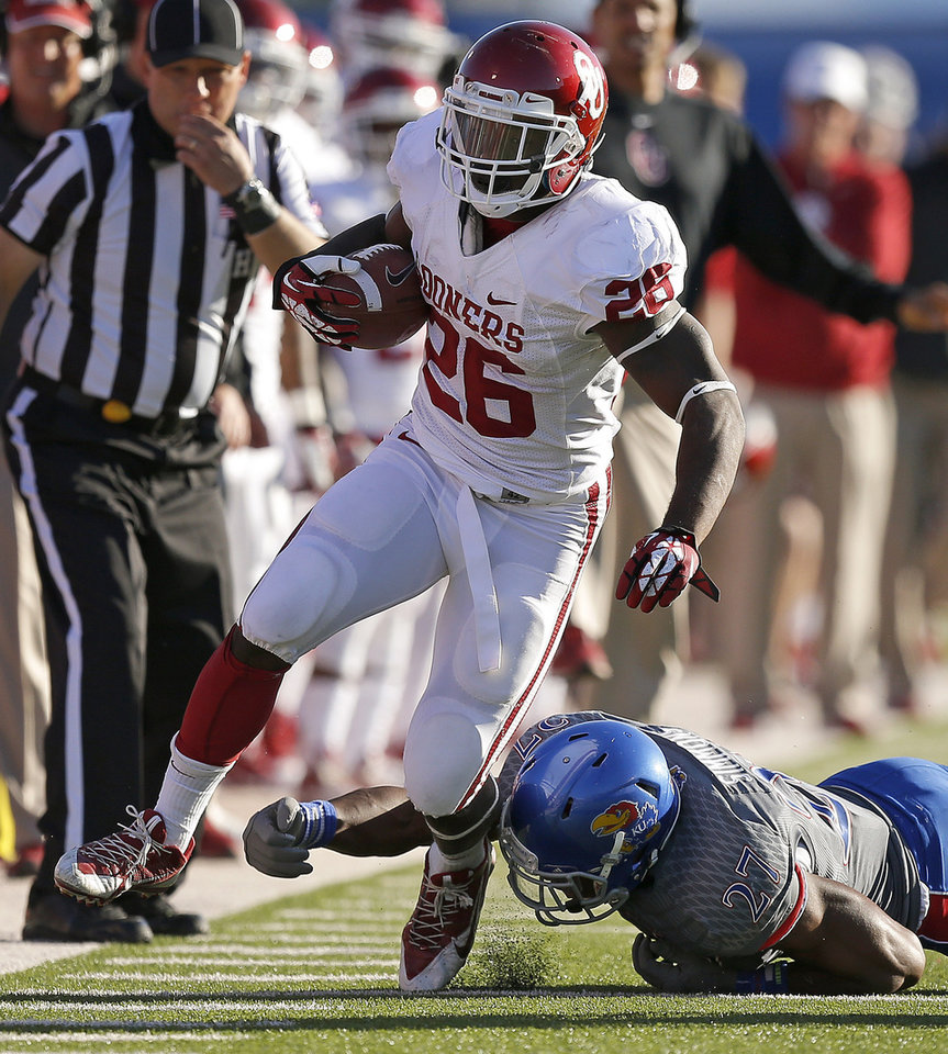 OU's Damien Williams (26) runs past KU's Victor Simmons (27) during the college football game between the University of Oklahoma Sooners (OU) and the University of Kansas Jayhawks (KU) at Memorial Stadium in Lawrence, Kan., Saturday, Oct. 19, 2013. Oklahoma won 34-19. Photo by Bryan Terry, The Oklahoman