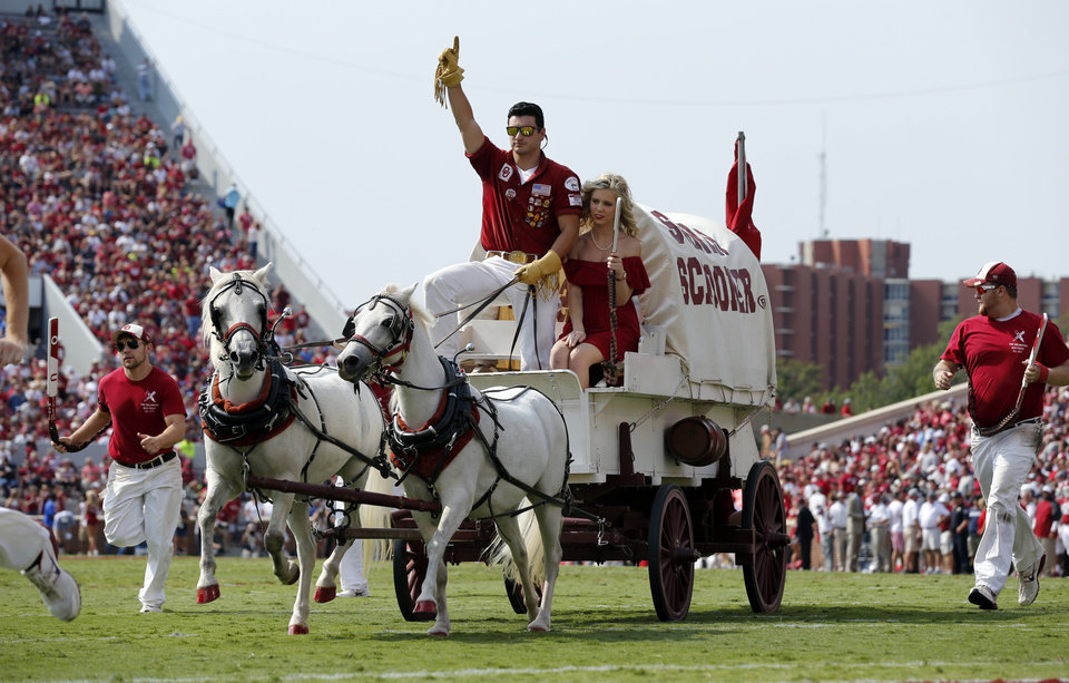 Photo - The Sooner Schooner makes a run during a college football game between the University of Oklahoma Sooners (OU) and the Tulsa Golden Hurricane (TU) at Gaylord Family-Oklahoma Memorial Stadium in Norman, Okla., on Saturday, Sept. 14, 2013. Photo by Steve Sisney, The Oklahoman
