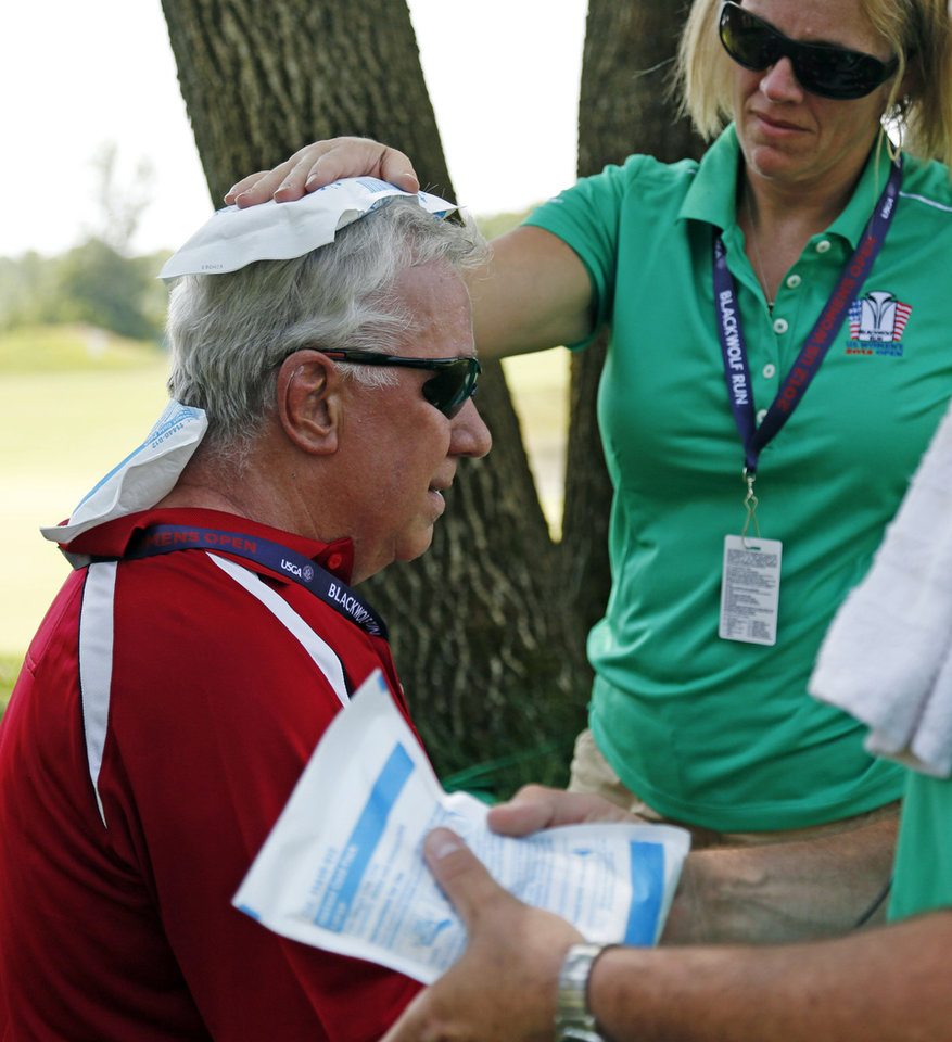 Photo -   A marshal is treated for heat exhaustion on the 18th green during the first round of the U.S. Women's Open golf tournament, Thursday, July 5, 2012, in Kohler, Wis. Oppressive heat is slamming the middle of the country with record temperatures that aren't going away after the sun goes down. (AP Photo/Jeffrey Phelps)
