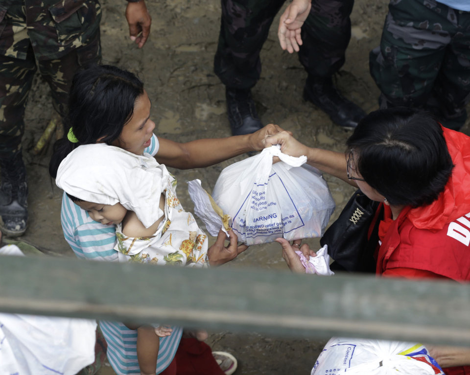 Photo - Typhoon victims receive relief goods following the visit of Philippine President Benigno Aquino III at New Bataan township, Compostela Valley in southern Philippines Friday Dec. 7, 2012. More than 310,000 people have lost their homes since Typhoon Bopha struck Tuesday and are crowded inside evacuation centers or staying with their relatives, relying on food and emergency supplies being rushed in by government agencies and aid groups. (AP Photo/Bullit Marquez)
