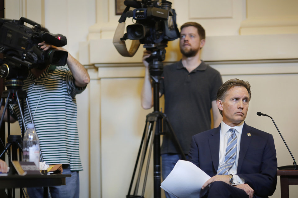 Photo - Hunter casts his eyes toward members of the State Election Board while he listens as Chairman Steve Curry advises attorney Garry Gaskins to narrow his focus of questioning. Oklahoma Attorney General Mike Hunter can remain on the ballot after the Oklahoma Election Board voted 3-0 on Monday, April 23, 2018, to deny a challenge to his candidacy on residency grounds. Hunter, a Republican, testified he always kept Oklahoma as his permanent home even though he lived in Virginia for years while working in Washington, D.C. for two trade organizations.